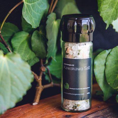 kawakawa salt grinder on a table surrounded by kawakawa branches